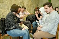 6 kişi karşılıklı sandalyelerde otururken görülmekte. sağ tarafta Oğuzhan ve Amine Elnur oturmakta.