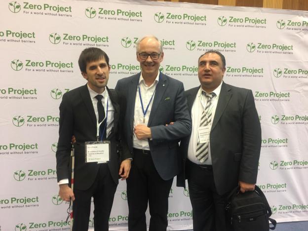 ZeroProject logolu beyaz büyük branda afişi önünde; İbrahim Elibal sağda, Martin Essl ortada, Emre Taşgın solda, yan yana ayakta durup gülümserken görülmekteler.